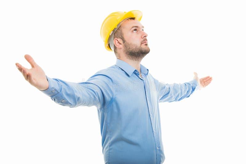 Arquitecto de la vista lateral con el casco amarillo que se coloca con los brazos abiertos fotos de archivo