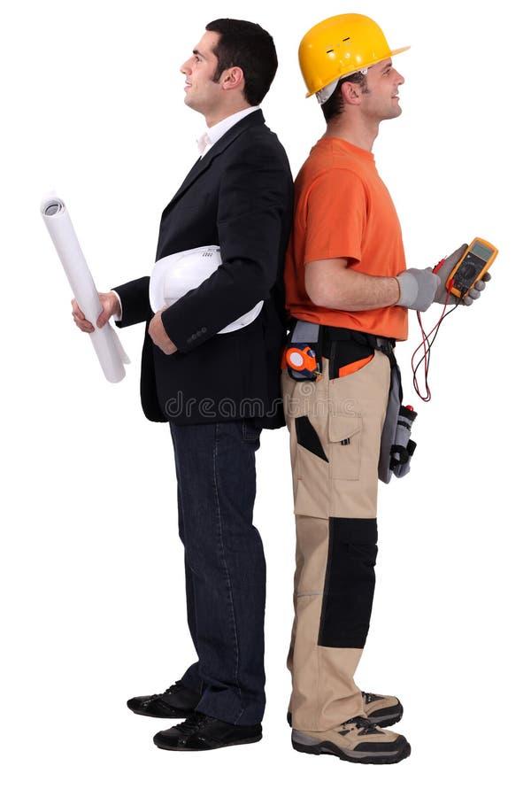 Arquitecto de pie con el electricista foto de archivo