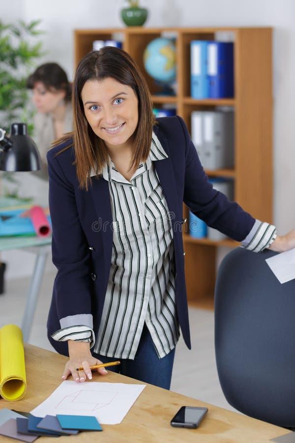 Arquitecto de sexo femenino feliz que trabaja en oficina fotografía de archivo