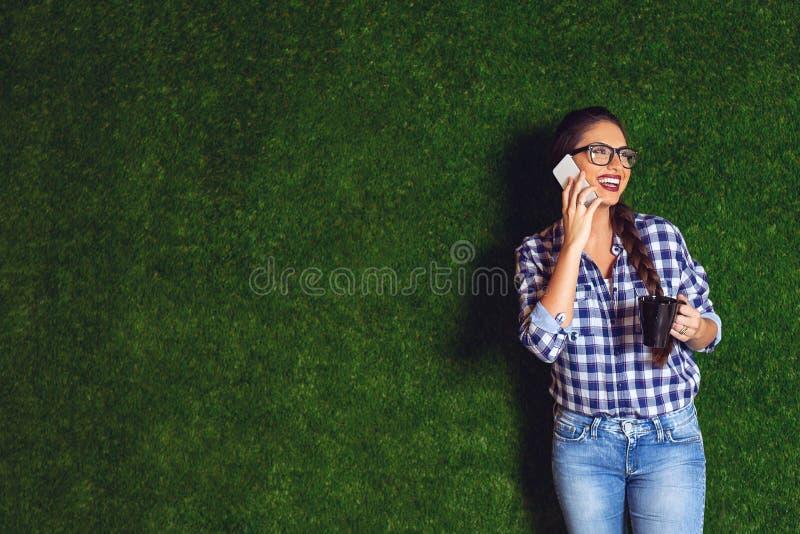 Arquitecto de sexo femenino hermoso en un descanso para tomar café, hablando en un teléfono imagenes de archivo