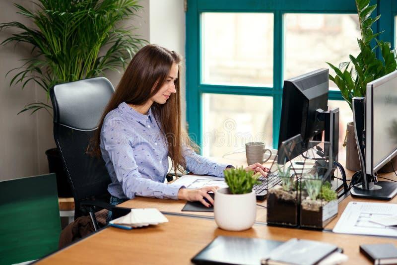 Arquitecto de sexo femenino joven atractivo en el funcionamiento azul de la camisa en la oficina moderna foto de archivo