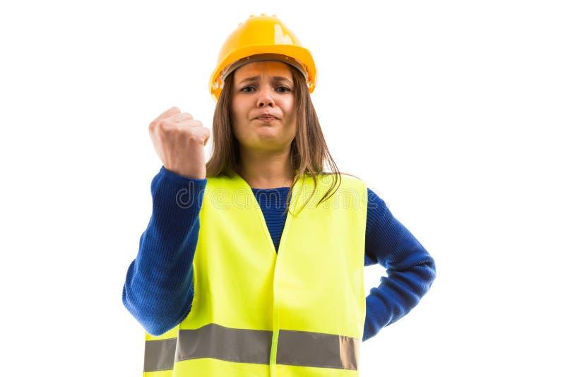 Arquitecto de sexo femenino joven enojado que muestra el puño imagen de archivo