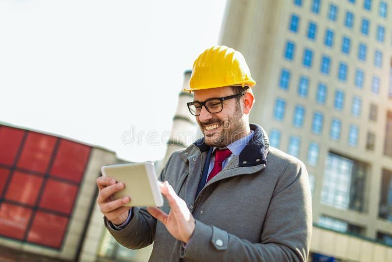 Arquitecto en casco protector usando la tableta digital imágenes de archivo libres de regalías