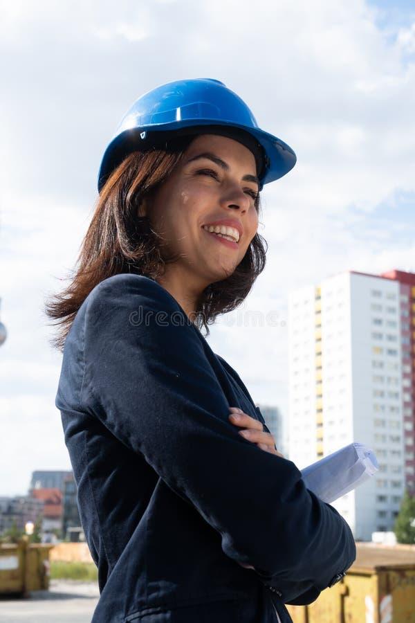 Arquitecto encantador de la mujer que presenta con los brazos doblados foto de archivo libre de regalías