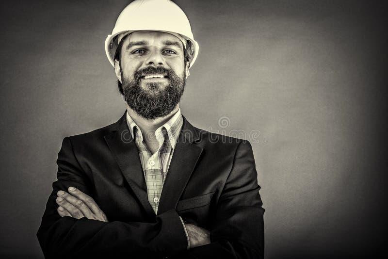 Arquitecto joven feliz con el casco de protección y los brazos doblados foto de archivo libre de regalías