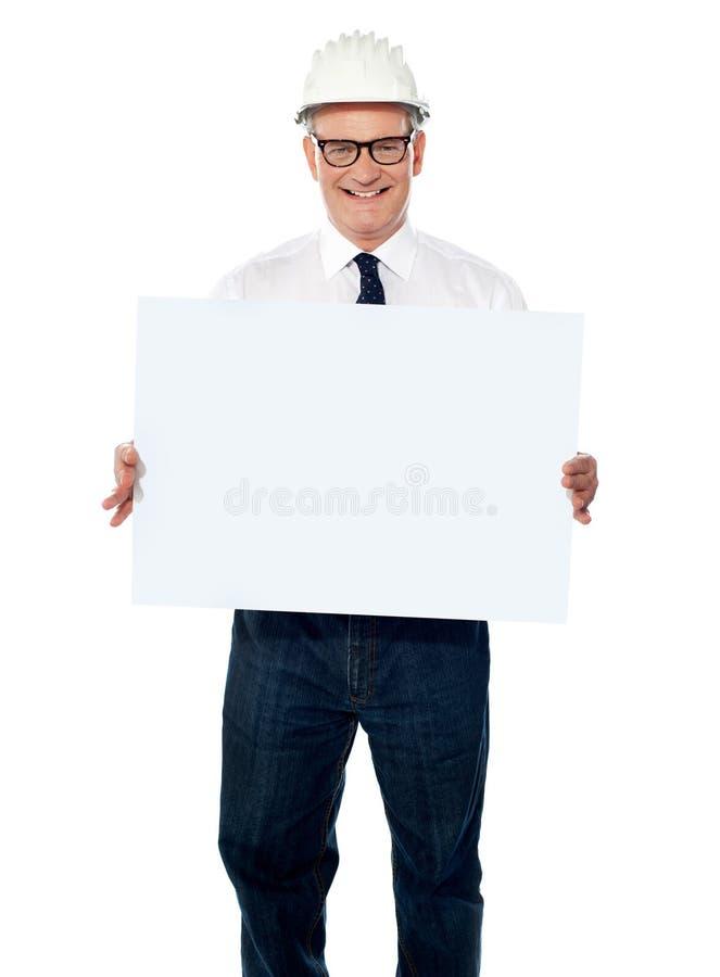 Arquitecto mayor que sostiene la cartelera en blanco foto de archivo libre de regalías