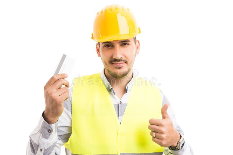 Arquitecto o contratista que celebra mostrar la tarjeta del debe-haber imagenes de archivo