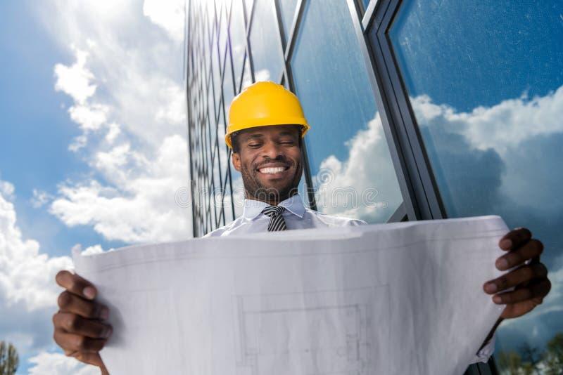 Arquitecto profesional en el casco que sostiene el modelo fuera del edificio moderno imagen de archivo libre de regalías