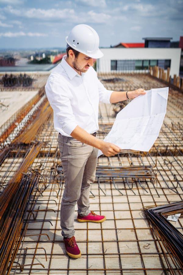 Arquitecto que mira los planes de papel en emplazamiento de la obra Detalles del edificio de la construcción y trabajadores imagen de archivo