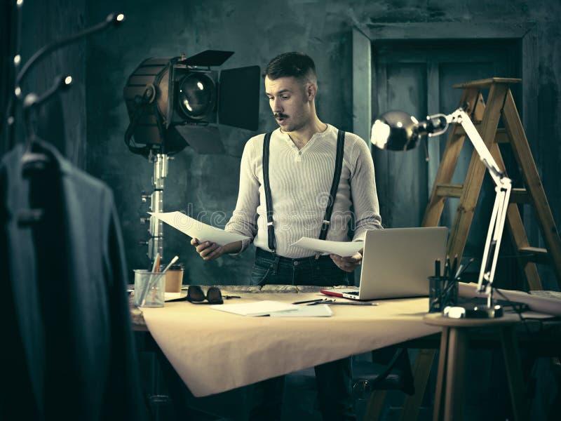 Arquitecto que trabaja en la tabla de dibujo en oficina foto de archivo libre de regalías