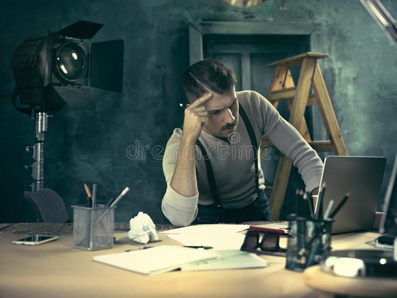 Arquitecto que trabaja en la tabla de dibujo en oficina foto de archivo