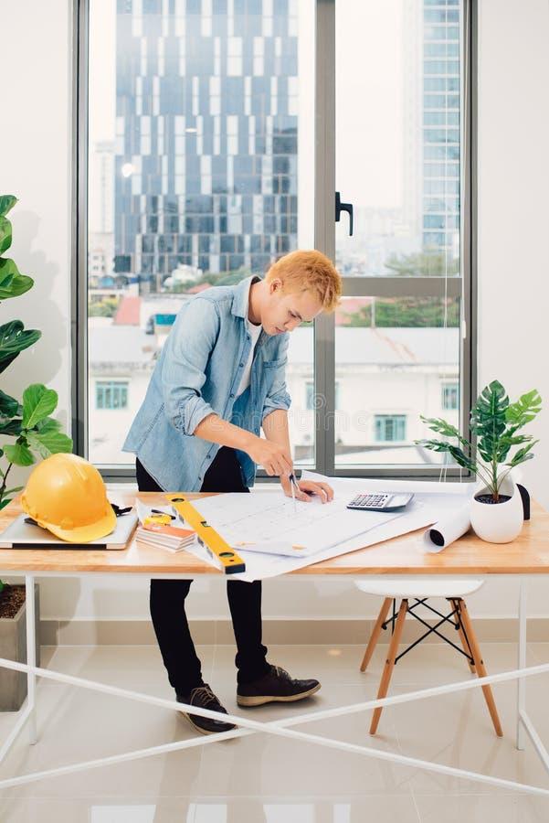 Arquitecto que trabaja en la tabla de dibujo en oficina fotos de archivo