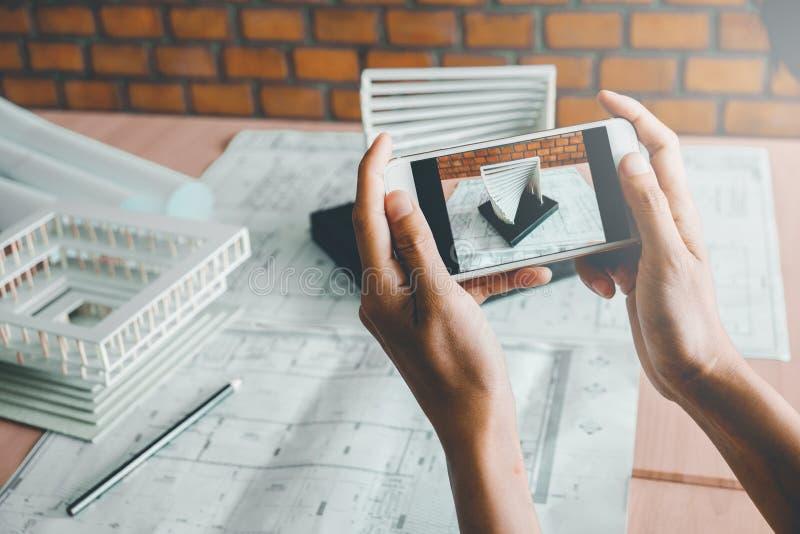 Arquitecto que usa el edificio modelo de la fotografía elegante del teléfono en oficina foto de archivo libre de regalías