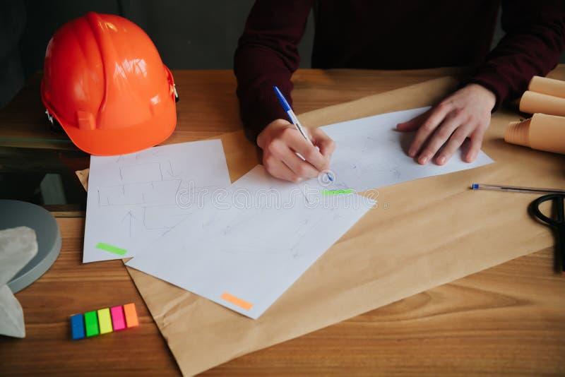 Arquitectos del concepto, pluma de tenencia del ingeniero señalando a arquitectos del equipo en el escritorio con un modelo en la imagenes de archivo