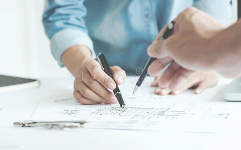 Arquitectos del ingeniero que discuten en la tabla con el modelo imagen de archivo libre de regalías