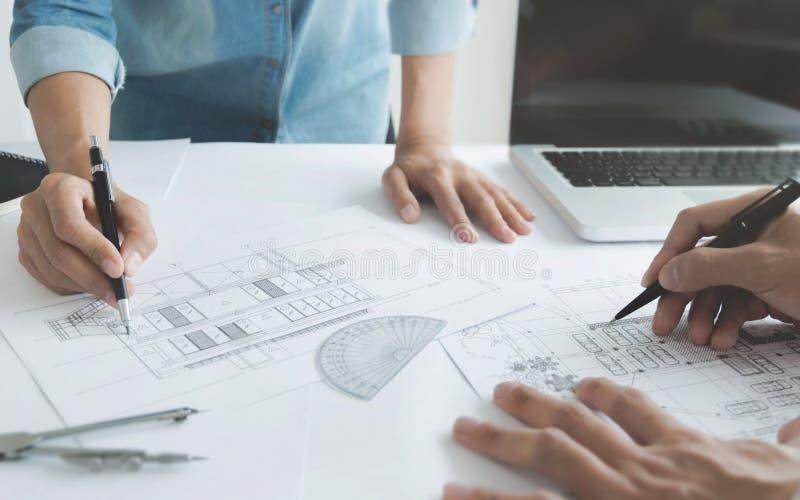 Arquitectos del ingeniero que discuten en la tabla con el modelo fotografía de archivo