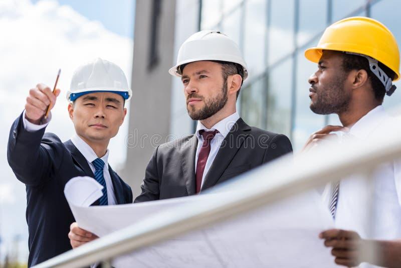 Arquitectos en los cascos de protección que trabajan con el modelo fuera del edificio moderno imagenes de archivo