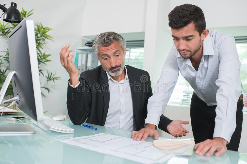 Arquitectos preocupados que miran planes en oficina fotos de archivo