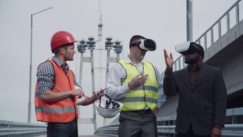 Arquitectos que discuten proyecto en auriculares de la realidad virtual foto de archivo