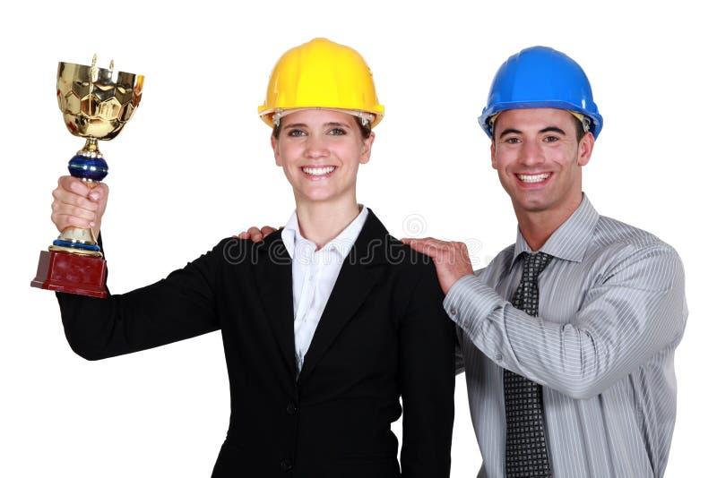 Arquitectos que sostienen un trofeo. imagenes de archivo