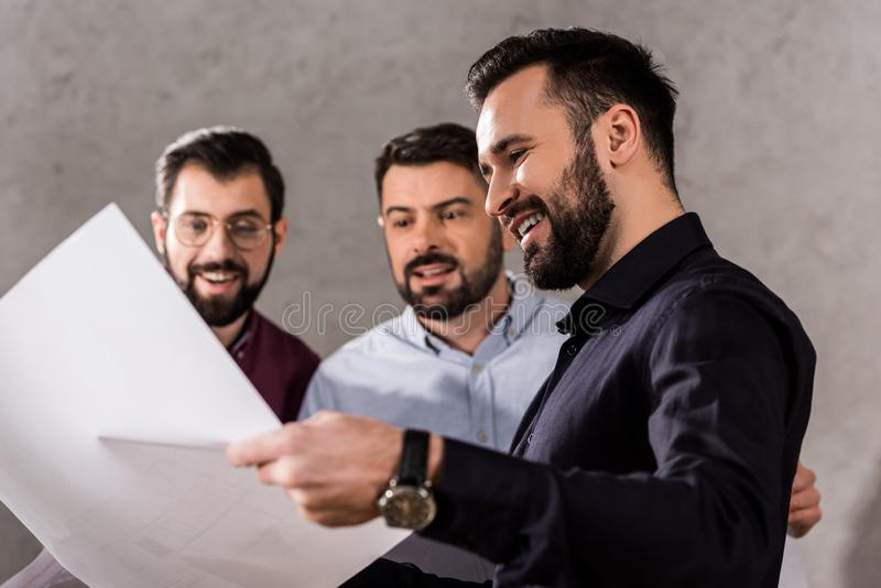 arquitectos sonrientes que miran modelos imagenes de archivo