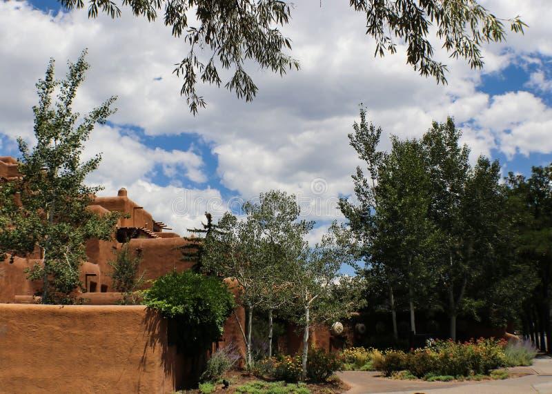 Arquitectura al sudoeste del adobe debajo de un cielo azul con las nubes blancas mullidas y rodeado y enmarcado por los árboles fotografía de archivo libre de regalías