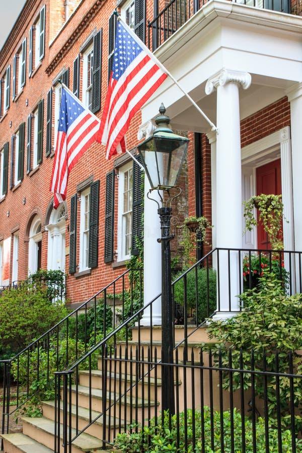 Arquitectura colonial del ladrillo con las banderas americanas foto de archivo