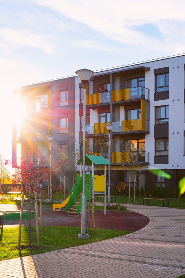 Arquitectura de la fachada de la casa del apartamento y luz residenciales del sol del patio del niño foto de archivo libre de regalías
