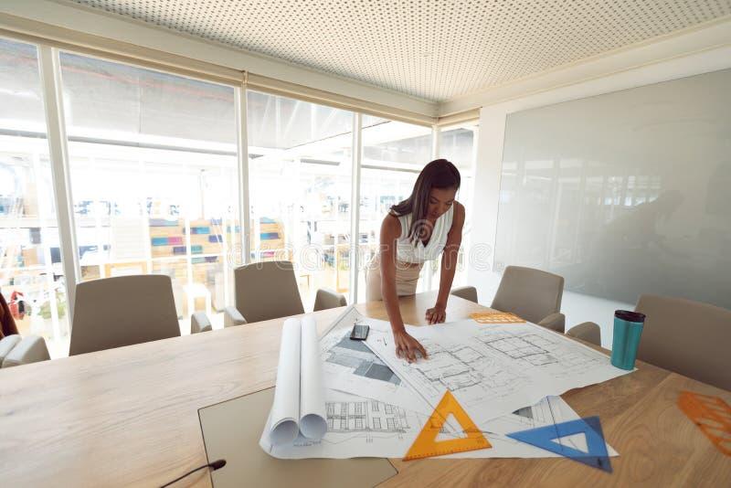 Arquitectura femenina que trabaja en modelo en la tabla en una oficina moderna fotos de archivo