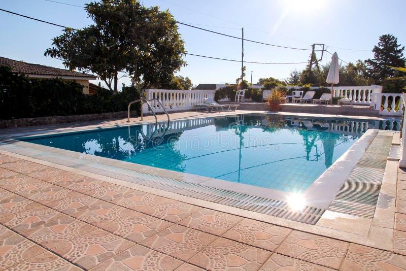 Arquitectura moderna de la casa del diseño de lujo de la piscina Agua y paraguas imagen de archivo libre de regalías