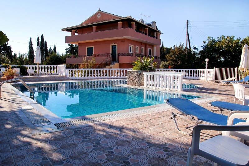 Arquitectura moderna de la casa del diseño de lujo de la piscina Agua y paraguas imágenes de archivo libres de regalías