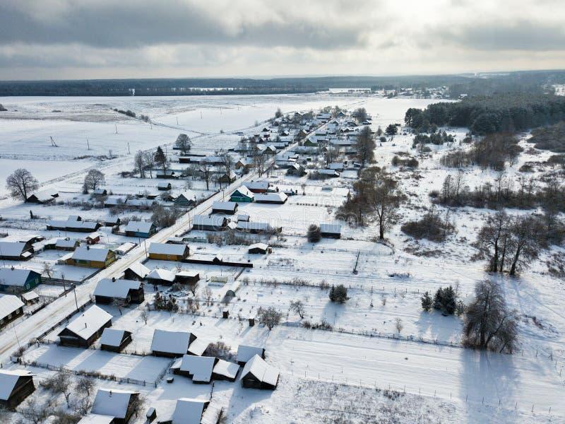 Arquitectura tradicional rusa Coverd del pueblo por la nieve Silueta del hombre de negocios Cowering imagen de archivo libre de regalías