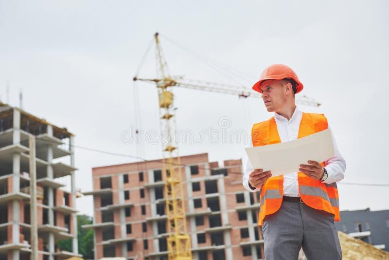 Arquitectura y concepto casero de la renovación - hombre en casco y guantes con el modelo en fábrica fotos de archivo libres de regalías