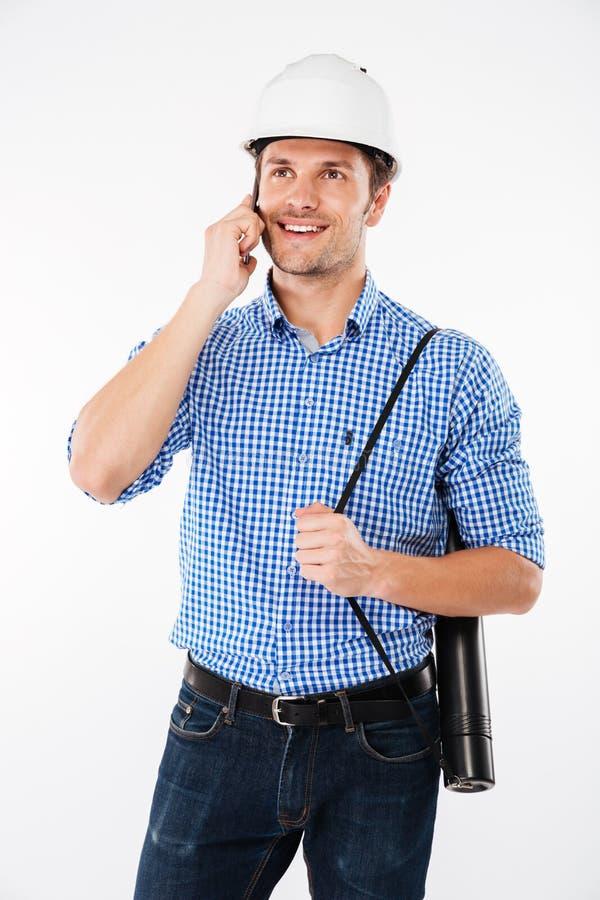 Arquiteto alegre do homem no capacete da construção que fala no telefone celular imagens de stock royalty free