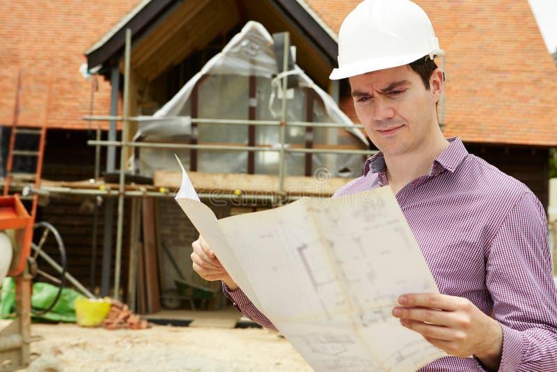 Arquiteto On Building Site que olha planos da casa imagem de stock royalty free