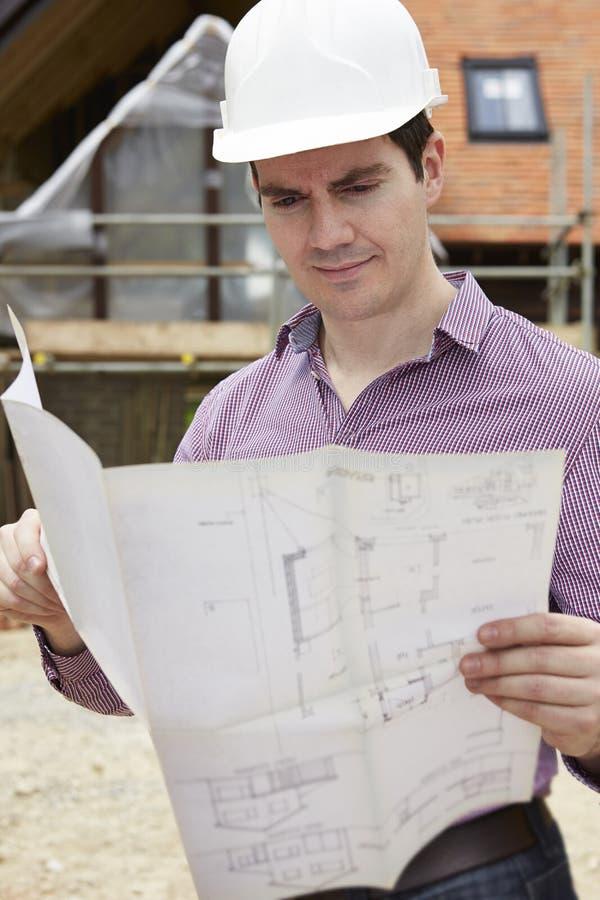 Arquiteto On Building Site que olha planos da casa imagem de stock