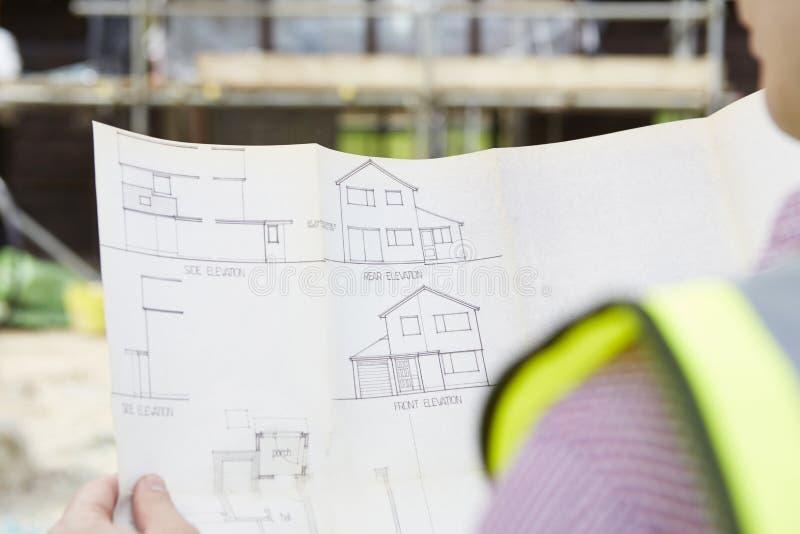 Arquiteto On Building Site que olha planos para a casa imagem de stock