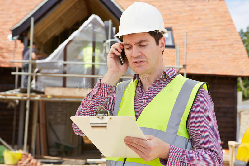 Arquiteto On Building Site que usa o telefone celular fotografia de stock royalty free