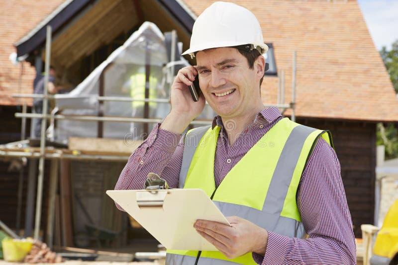 Arquiteto On Building Site que usa o telefone celular fotos de stock