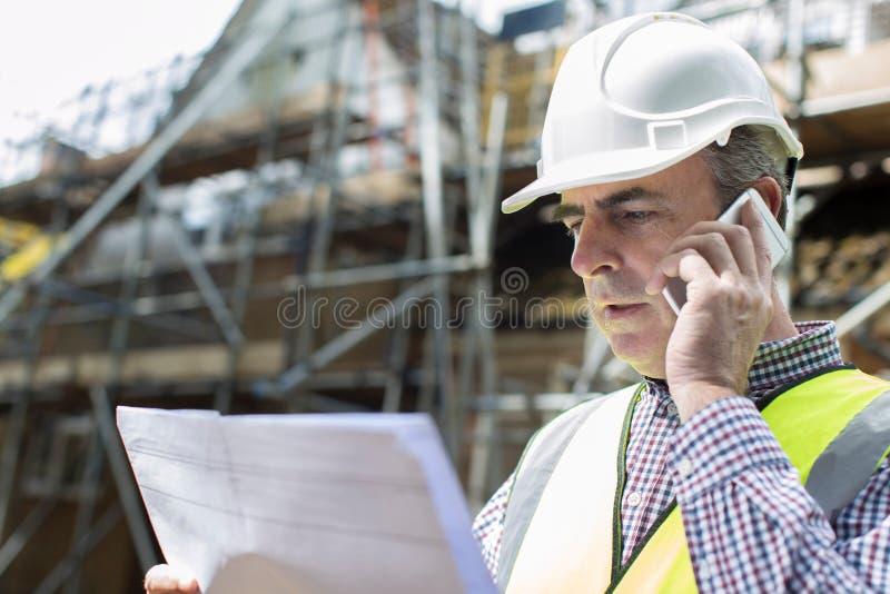 Arquiteto On Building Site que usa o telefone celular imagens de stock royalty free
