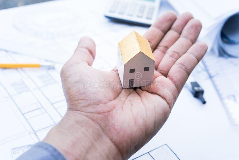 Arquiteto com modelo da casa pequena disponível e projeto de plano fotos de stock royalty free