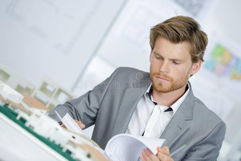 Arquiteto com modelos e mesa de escritório imagem de stock