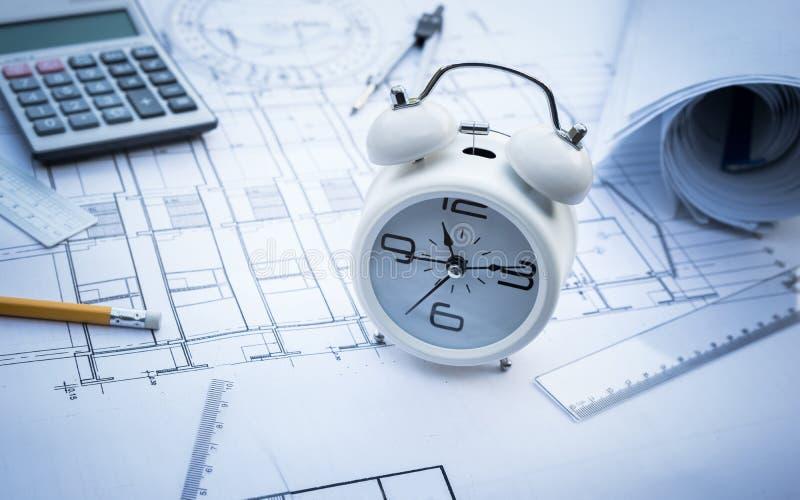 Arquiteto com o despertador no papel do projeto de plano imagem de stock