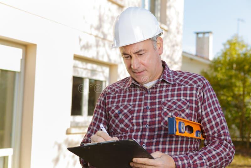 Arquiteto com a prancheta no capacete de segurança no canteiro de obras imagens de stock