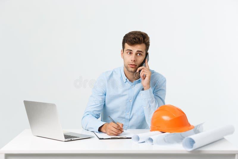 Arquiteto confiável Homem novo considerável com capacete de segurança e modelo e fala no telefone celular ao sentar-se no seu fotografia de stock royalty free