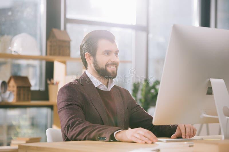 arquiteto considerável que trabalha com o computador no escritório fotos de stock