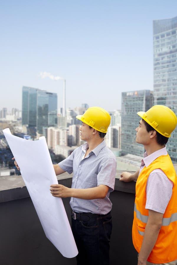 Arquiteto And Construction Worker que fala e que olha o modelo no telhado, cidade no fundo imagem de stock