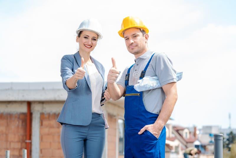 Arquiteto e trabalhador da construção no local que dá os polegares-acima foto de stock royalty free