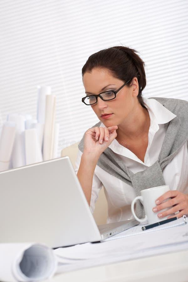 Arquiteto fêmea com assento do portátil e do café foto de stock