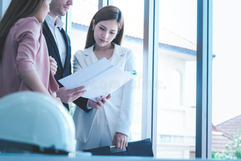 Arquiteto fêmea que mostra a seu chefe os bens imobiliários que constroem o pl foto de stock